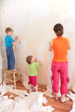 Mother with children remove old wallpapers Royalty Free Stock Photography