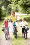 Mother and children riding bikes in countryside Royalty Free Stock Image