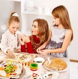 Mother and children rolling dough in the kitchen. Royalty Free Stock Image