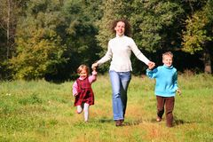 Mother with children run in wood Stock Photo