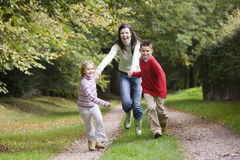 Mother and children running along woodland path. In autumn Royalty Free Stock Image