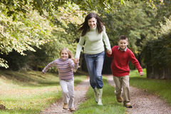 Mother and children running along woodland path. In autumn Royalty Free Stock Photography