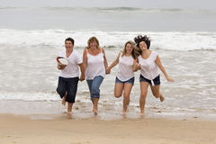 Mother and children running on the beach Stock Image