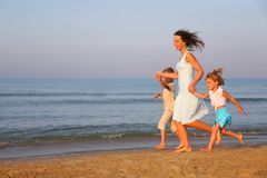 Mother with children running on edge of sea stock photos