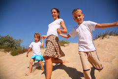 Mother with children runs on sand. Summer Stock Image
