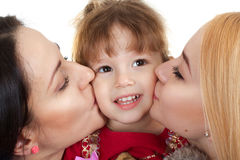 Mother and children. Mother and sister kiss on the cheek of a little girl  on white background Royalty Free Stock Photo