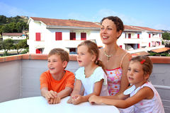 Mother and children sit in day-time on balcony Royalty Free Stock Photography