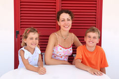 Mother with children sit near shut door to table stock photo