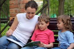 Mother with children sit and read book Stock Image