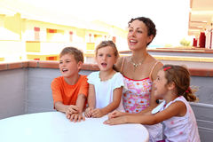 Mother and children sit on verandah in summer Royalty Free Stock Image