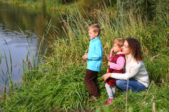 Mother with children sits on bank of pond Stock Photography