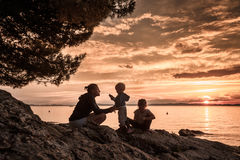 Mother with children sitting on beach, talking and playing royalty free stock photo