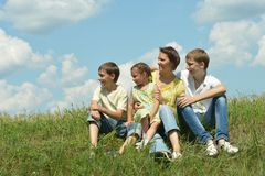 Mother and children sitting on grass Stock Photos
