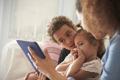 Mother And Children Sitting On Sofa Using Digital Tablet Royalty Free Stock Photography