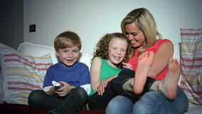Mother And Children Sitting On Sofa Watching TV Together