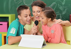 Mother and children singing karaoke. Mother and children sitting at table with tablet and singing karaoke Stock Images