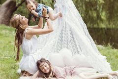 Mother and children are sitting in a tent teepee royalty free stock photo