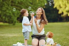 Mother with children with soap bubbles in  park. Mother with children with soap bubbles in summer park.  Mothers Day stock photos