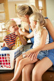 Mother And Children Sorting Laundry. Sitting On Kitchen Counter Stock Photo