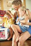 Mother And Children Sorting Laundry Stock Images