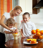Mother with children squeezed orange juice Royalty Free Stock Photos