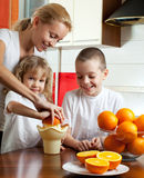 Mother with children squeezed orange juice Stock Photo