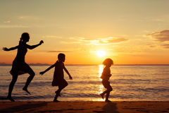 Mother and children standing on the beach at the sunset time. Stock Photo