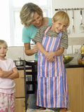 Mother and children (5-8) standing in kitchen, son (5-7) wearing striped apron, smiling, portrait stock images