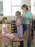 Mother and children (5-8) standing in kitchen, son (5-7) wearing striped apron, smiling, side view stock photography