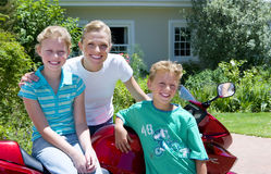 Mother and children (8-10) standing beside motorbike on driveway, smiling, portrait Stock Photo