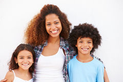 Mother And Children Standing Outdoors Against White Wall� stock images