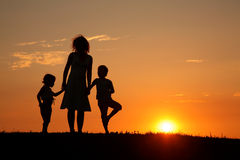 Mother and children on sunset silhouette Stock Photography