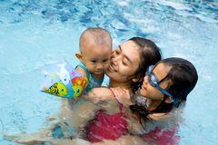 Mother and children swim together royalty free stock photo