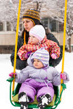 Mother and children in swing in winter Royalty Free Stock Photography