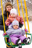 Mother and children in swing in winter Stock Photos