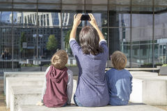 Mother and children taking selfie portrait on smartphone outdoors. Family, childhood, technology  people concept Royalty Free Stock Photography