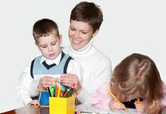 Mother and children together paint an album Royalty Free Stock Photos