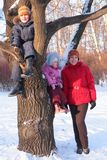 Mother with children on tree in winter Royalty Free Stock Photography