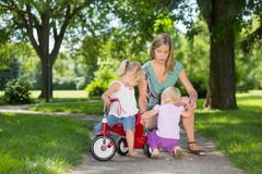 Mother And Children With Tricycle In Park. Mother and children with tricycle on walkway in park stock photo