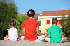 Mother with children turned the backs. Mother with two children turned the backs, sit in  pose of yoga and meditate Stock Photo