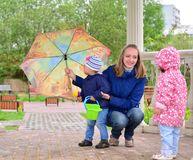 Mother with children and an umbrella in arbor Stock Photo