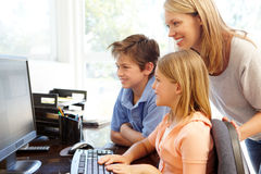 Mother and children using computer at home Stock Photo