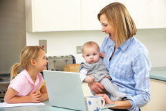 Mother with children using laptop in kitchen Stock Image