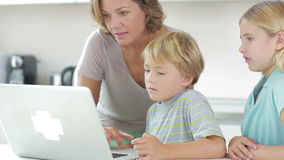 Mother and children using laptop Stock Photo