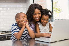 Mother and children using laptop Stock Photos