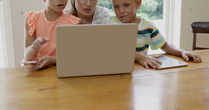 Mother and children using laptop. In the sitting room stock video