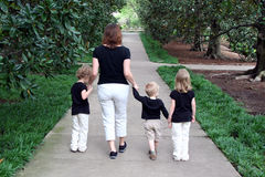 Mother and Children Walking. A mother walks hand in hand with her three children Royalty Free Stock Photography