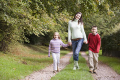 Mother and children walking along woodland path royalty free stock photography