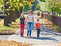 Mother with children walking in autumn park on sunny day Stock Images