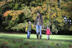 Mother and children walking in the park Stock Photography
